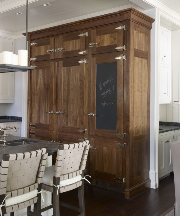 white kitchen with a steel gray custom apron front soapstone sink and a period ice-box look refrigeration armoire in natural wood - Hickman Interiors via Atticmag