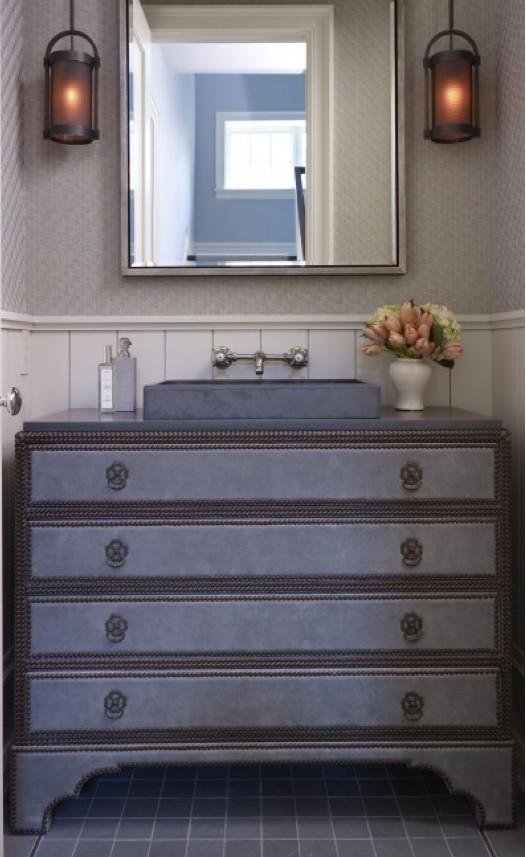 modern powder room sinks - upholstered powder room dresser vanity with nailhead trim and a shallow stone vessel sink - Hickman Interiors via Atticmag