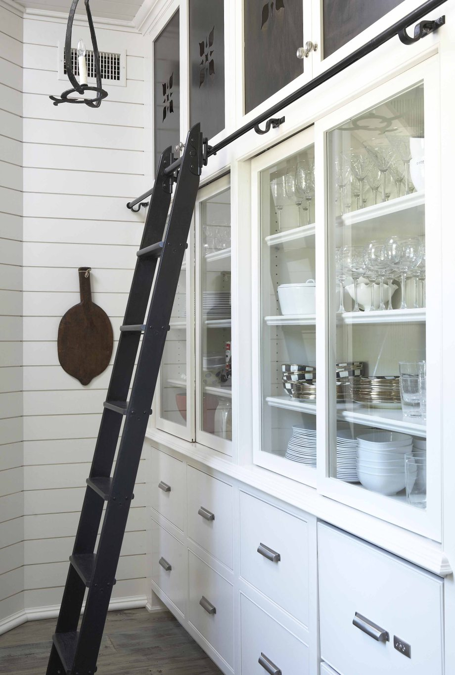 white shiplap kitchen - dish storage hutch with sliding library latter and pierced panel soffit cabinets - Tracery Interiors via Atticmag