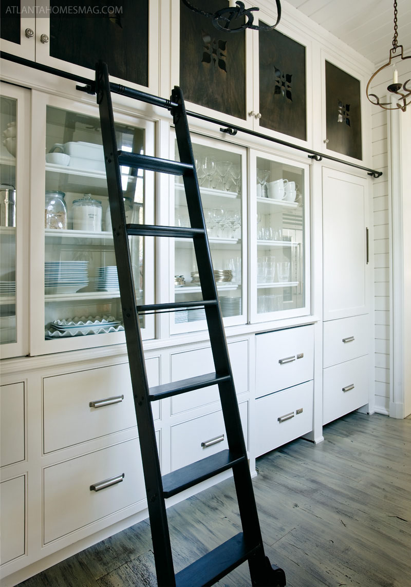 white shiplap kitchen - dish storage hutch with sliding library ladder, pierced panel soffit cabinets and a paneled SubZero - Tracery Interiors via Atticmag