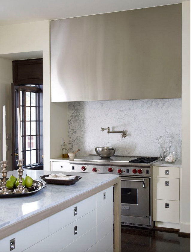 pale neutral kitchens - view of niche with Wolf range and stainless steel slab style hood and a corner of the island in an off white kitchen - Andrew Brown via Atticmag