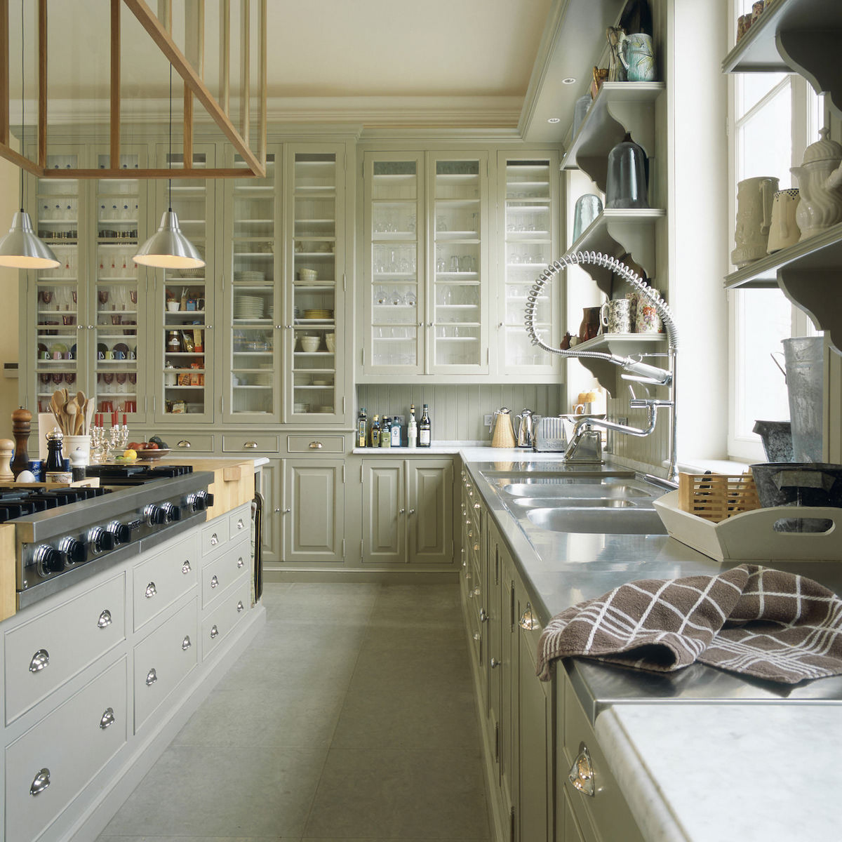 pale neutral kitchens - Light gray green Belgian kitchen with tall wall storage cabinets and a large island - Baden Baden via Atticmag