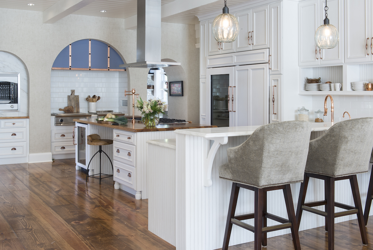 two kitchens - white DuraSupreme cabinet kitchen with Sub Zero refrigeration, La Cornue rotisserie, charbroiler, griddle and copper hardware, faucet and trim by Jenny Rausch - Karr Bick Kitchens via Atticmag