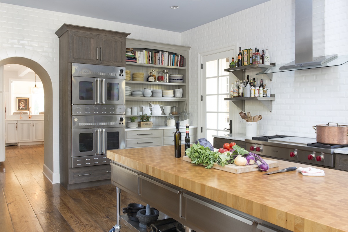 two kitchens - white working kitchen with DuraSupreme weathered cherry cabinets and custom island by Jenny Rausch - Karr Bick via Atticmag