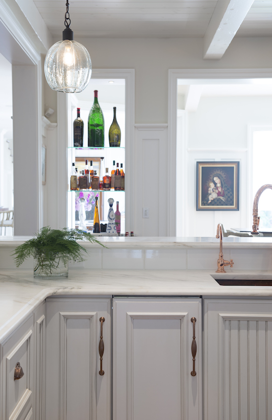 two kitchens - close up of Danby marble counters and copper sink with matching faucet and Scotsman ice maker in a white Dura Supreme cabinet kitchen by Jenny Rausch - Karr Bick via Atticmag