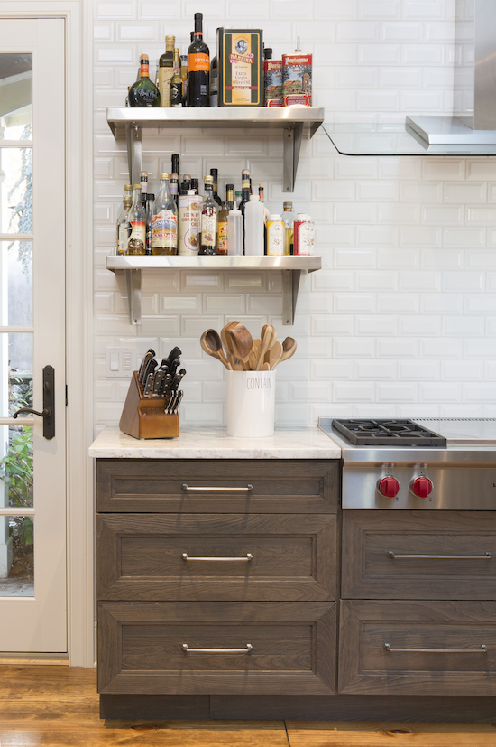 two kitchens - the work horse second kitchen by Jenny Rausch feature open shelving, a 48-inch Wolf rangetop and DuraSupreme Dalon cherry weathered cabinets with white quartzite counters - Karr Bick via Atticmag