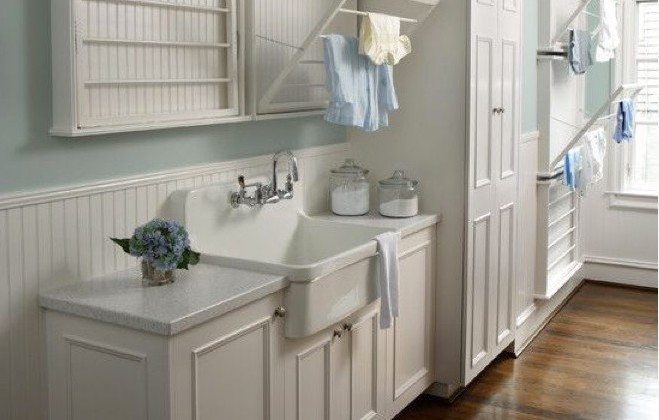 laundry room sink - Kohler Gilford vitreous china, 30-inch sink set in a custom cabinet in a coastal style laundry room - Rabaut Design via Atticmag