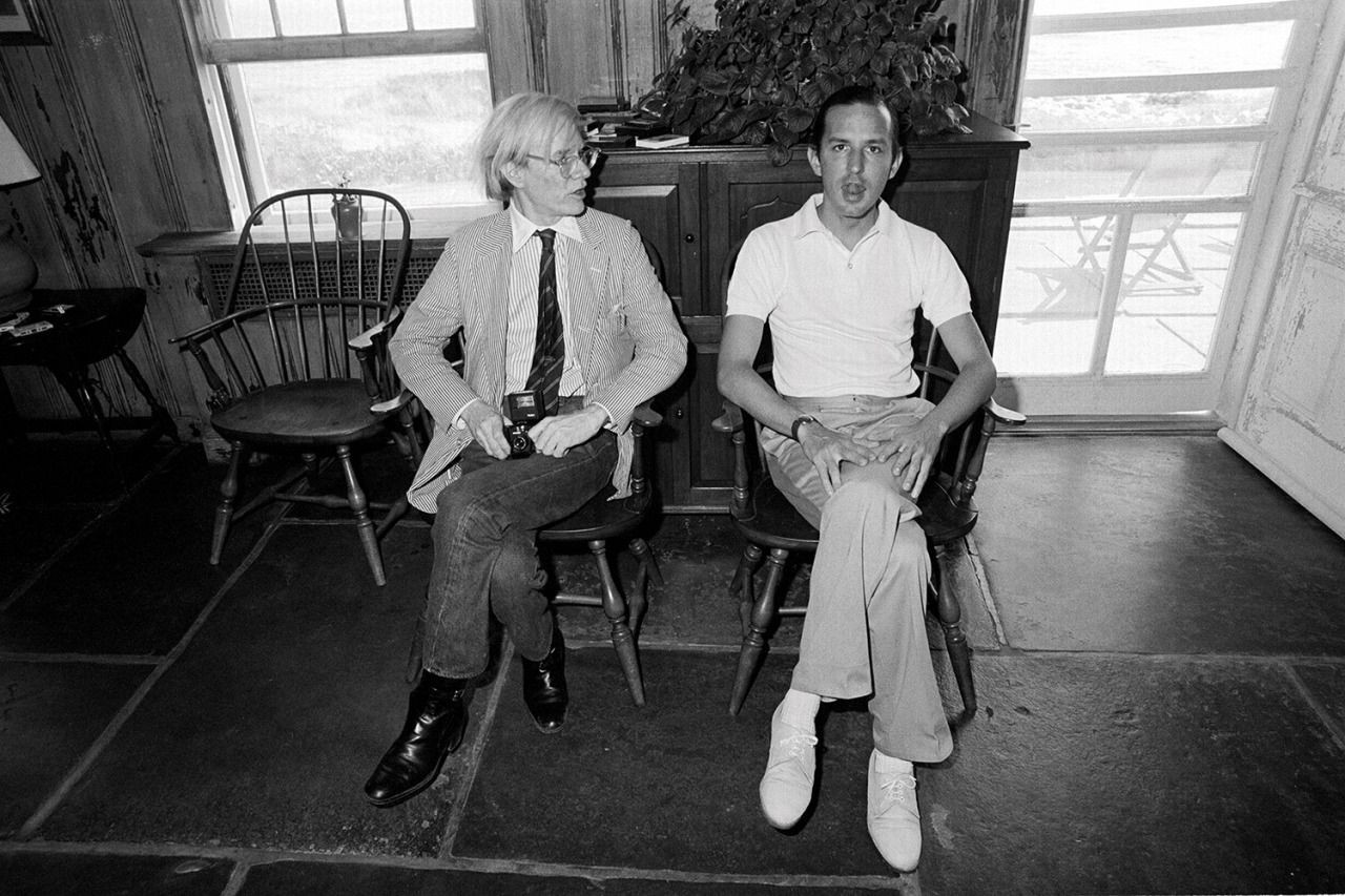 Andy Warhol beach house - The late Pop artist Andy Warhol holding his camera seated next to long time business manager, the late Fred Hughes, in mid-sentence - Douglas Elliman via Atticmag