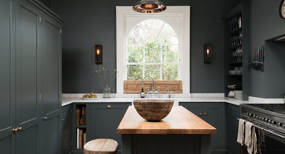deVol kitchen - View of sink wall and island with natural wood features in a deVol kitchen with Shaker cabinets in Flint gray - deVol Kitchens via Atticmag