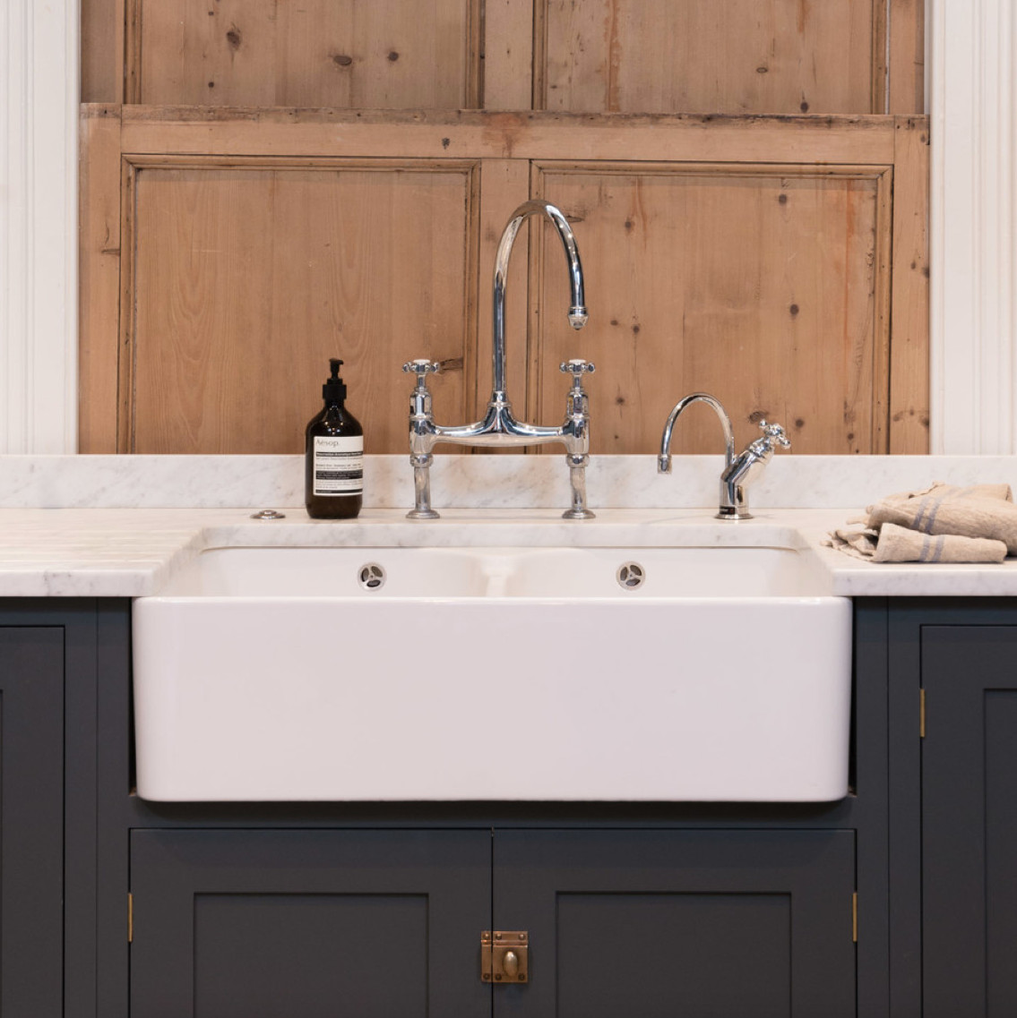 deVol kitchen - Double apron front sink with classic bridge faucet in a deVol kitchen with Shaker cabinets in Flint gray - deVol Kitchens via Atticmag