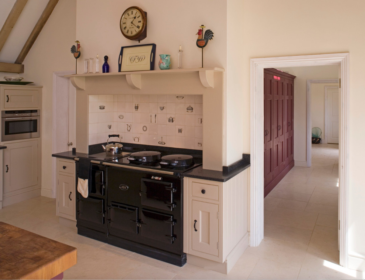 red barn kitchen - a black Aga cooker is set into a niche while beyond the kitchen the same crimson-color cabinets are repeated for storage - Thomas & Thomas via Atticmag