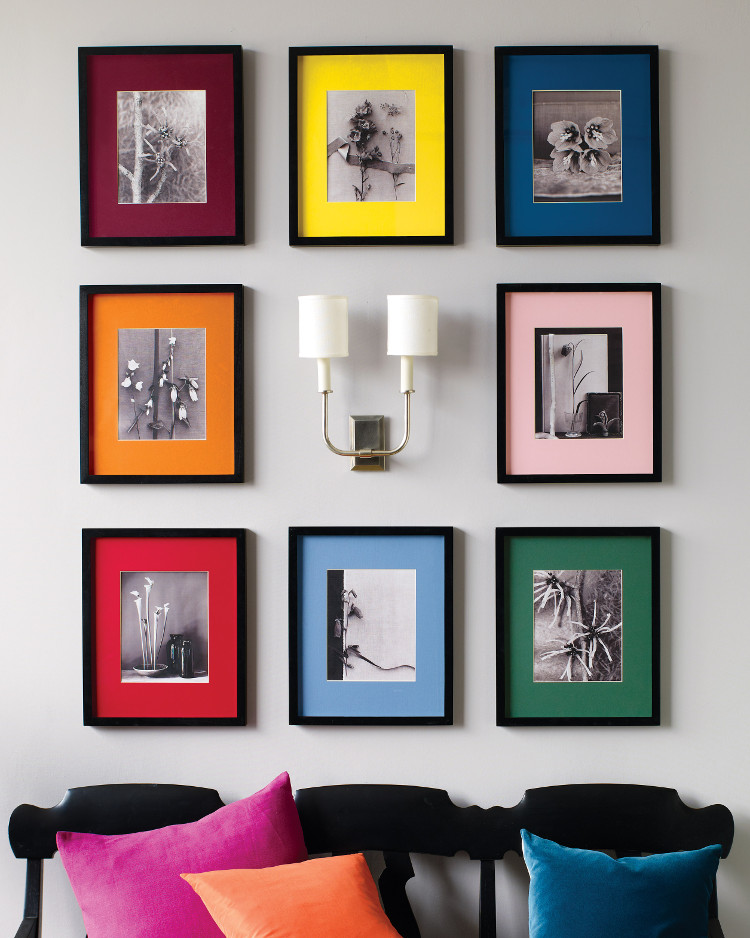 color picture wall - eight black and white images, in black frames, are enlivened by precut color picture mats from worldviewpic.com. The frame and matte colors are reinforced by the black-painted bench with bright pillows below - MarthaStewart.com via Atticmag