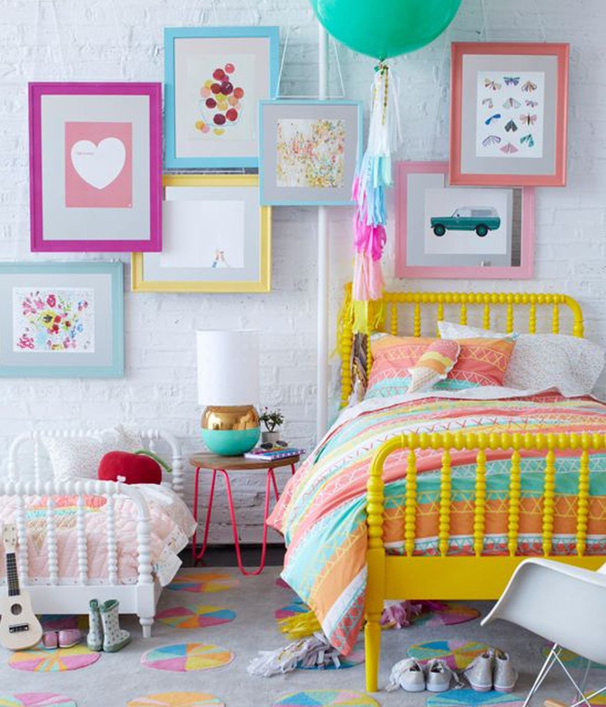 color picture wall - multi-color pastel picture frames, with colored prints, some hung overlapping on a white wall in a child's room with coordinating painted Victorian style Jenny Lind beds - Land of Nod via Atticmag