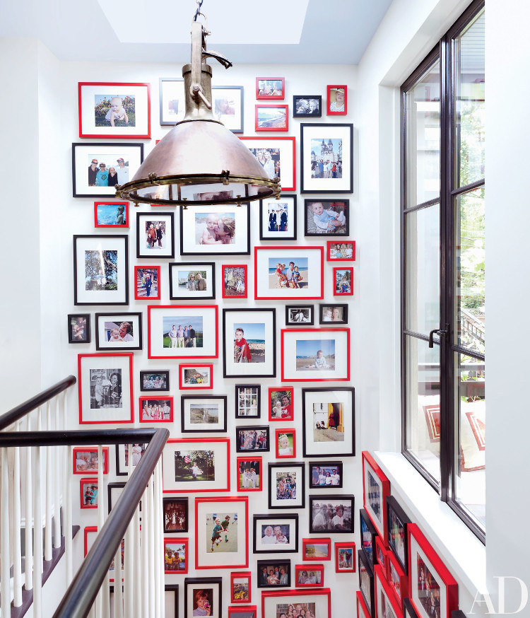 color picture wall - in a Brooklyn, NY house designed by Nick Olsen, family photos are hung two stories high in a stairwell with a lively mix of black and red frames - AD via Atticmag