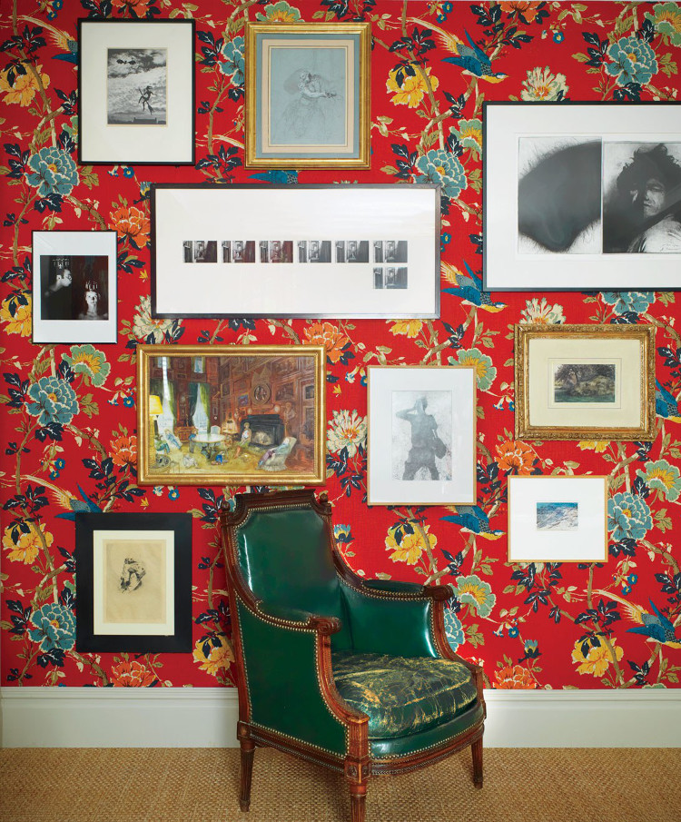 color picture wall - exotic large scale floral print wallpaper, with a lipstick red ground, in the master bedroom of Frédéric Malle's New York living room provides a vivid background for a mixed picture wall, including Duane Michaels photos, hung to also showcase a leather-upholstered Louis XVI bergère - AD via Atticmag