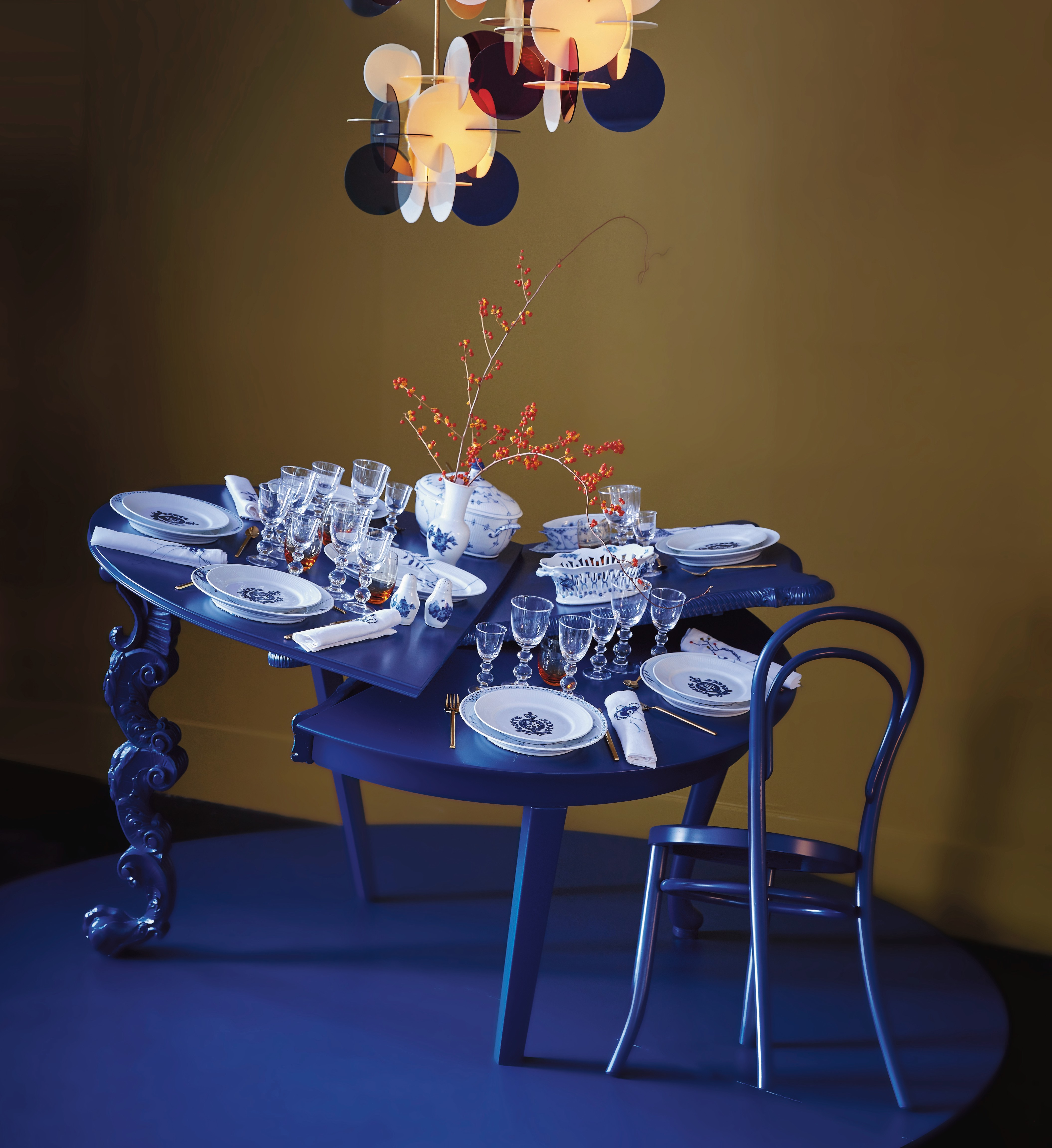 fashionable Christmas - a cobalt blue Christmas table by Baum & Pferdgarten is deconstructed into three tilted sections and set with Blue Fluted Plain and Half Lace china - Royal Copenhagen via Atticmag