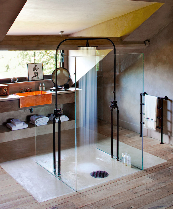 freestanding showers - in a Swiss master bath a pair of dark tone shower towers are joined by an arc of pipe with a single rainshower head - AD Russia via Atticmag