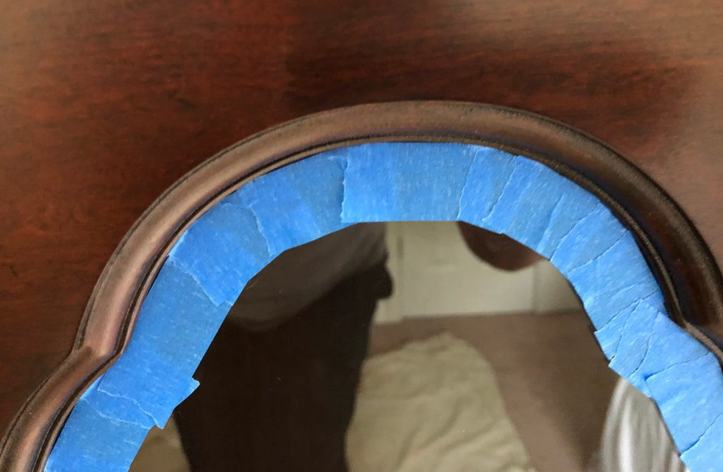 repurposed china cabinet - taping the curved tops of the glass doors - Atticmag