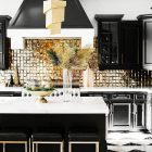 gold tile kitchen backsplash kitchen with black cabinets and black and white floor by erin melkonian designs - Arteriors via Atticmag