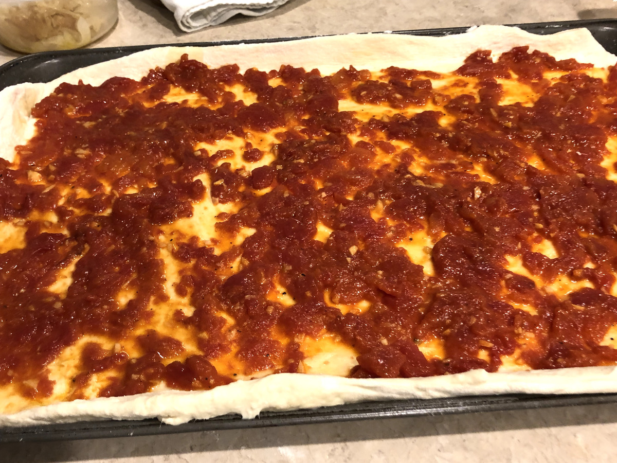 summer pizza - tomato sauce spread over the dough - Atticmag